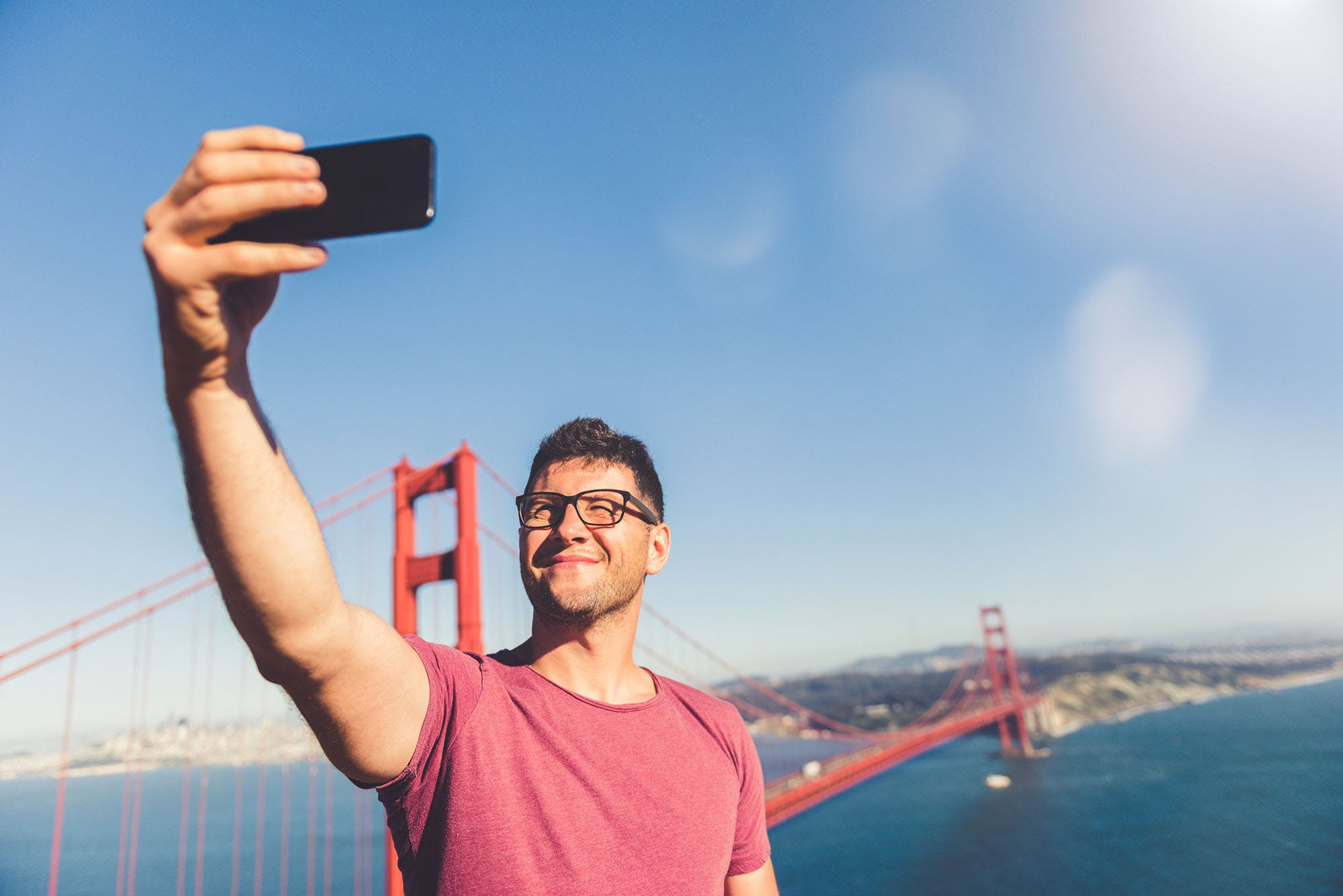 Young man taking a selfie by the Golden Gate Bridge in San Francisco