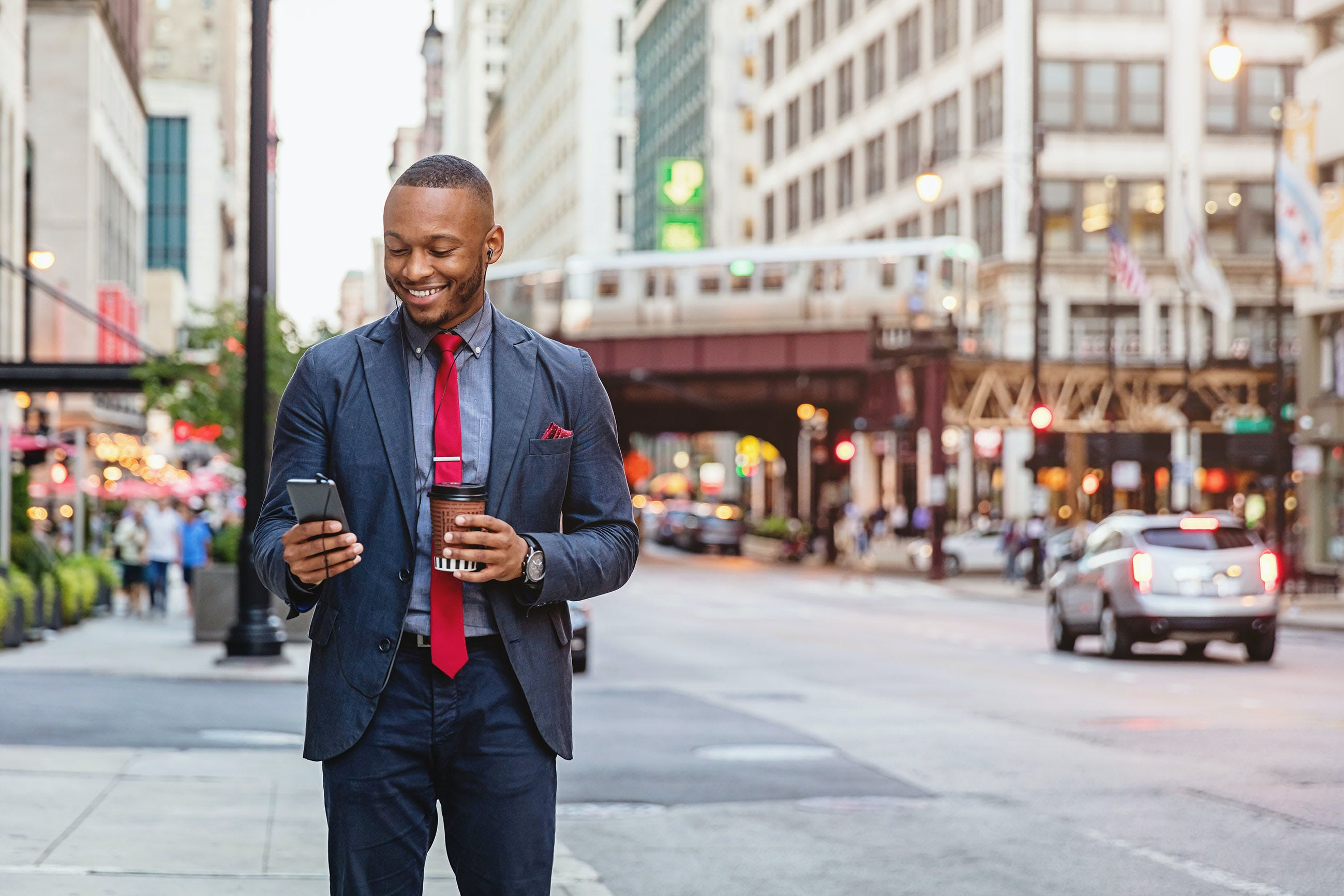 Smiling business commuter using smart phone chicago streets