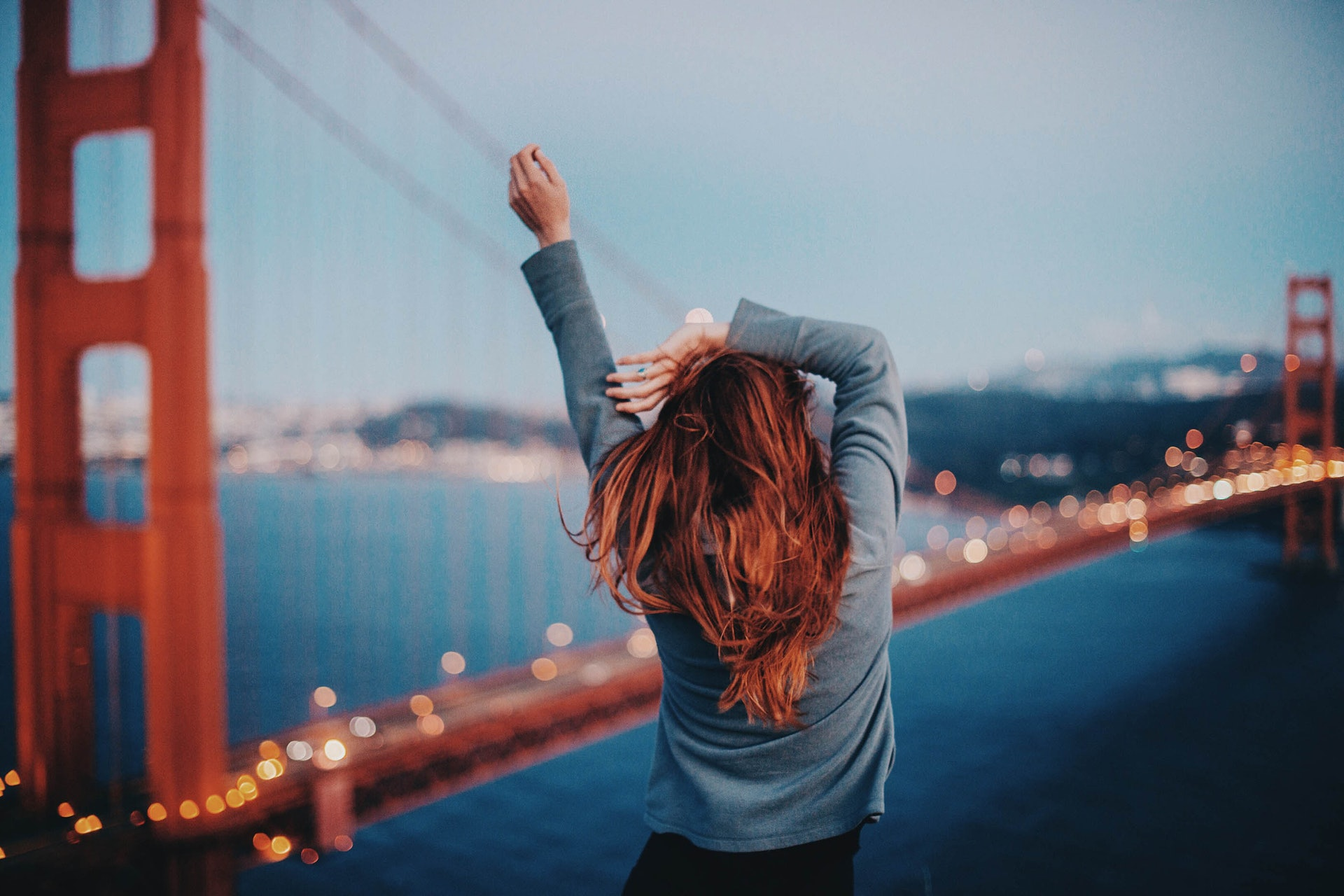 Young woman with Golden Gate Bridge in the background, San Francisco