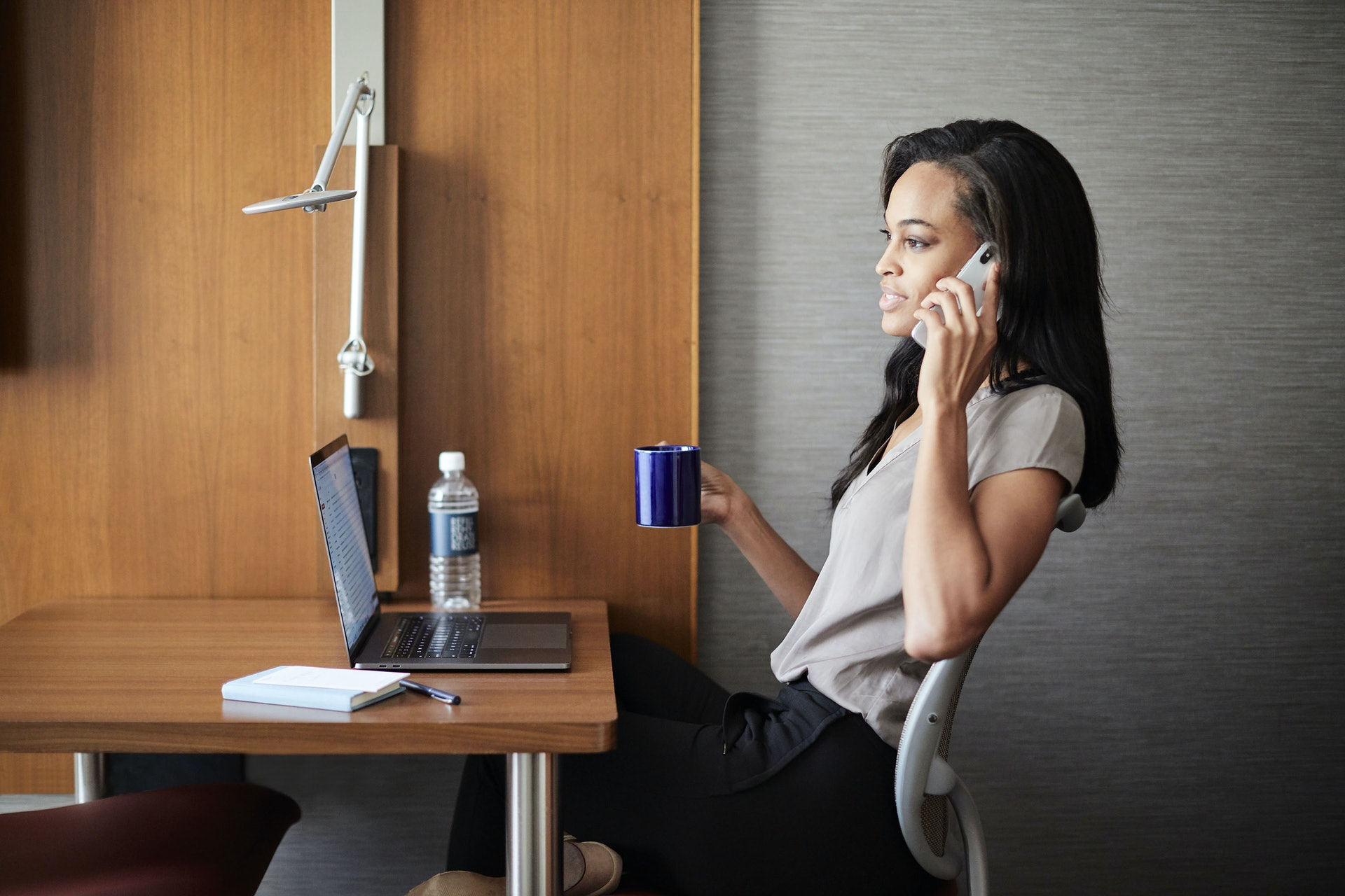 Girl talking on phone while working on laptop