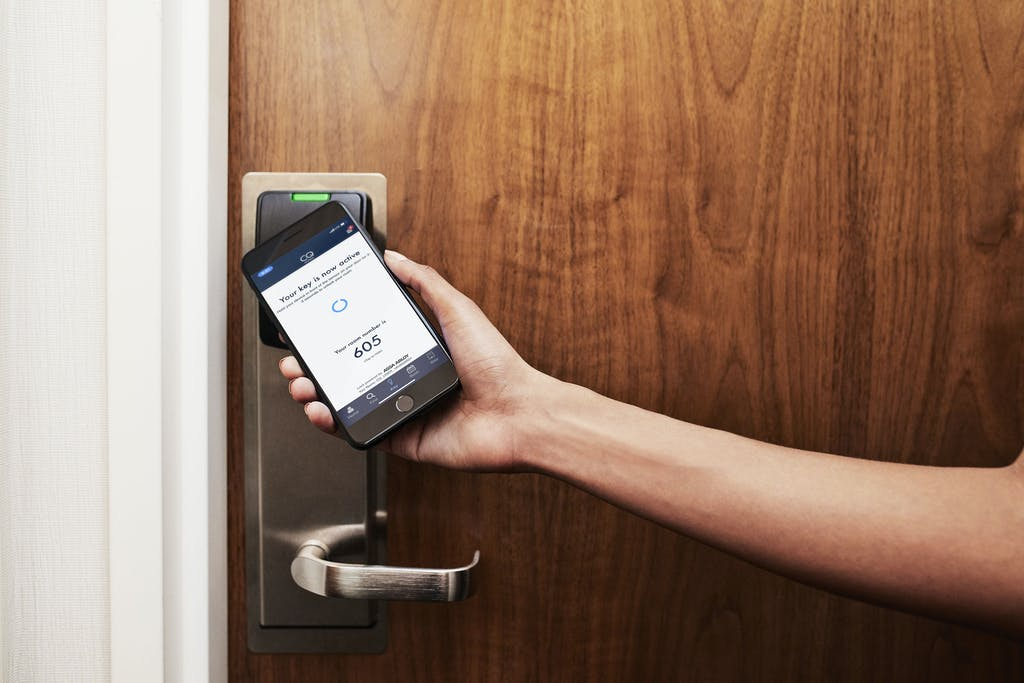 Using the CQ Hotel App on a smartphone to open the guest room door at Club Quarters Hotels