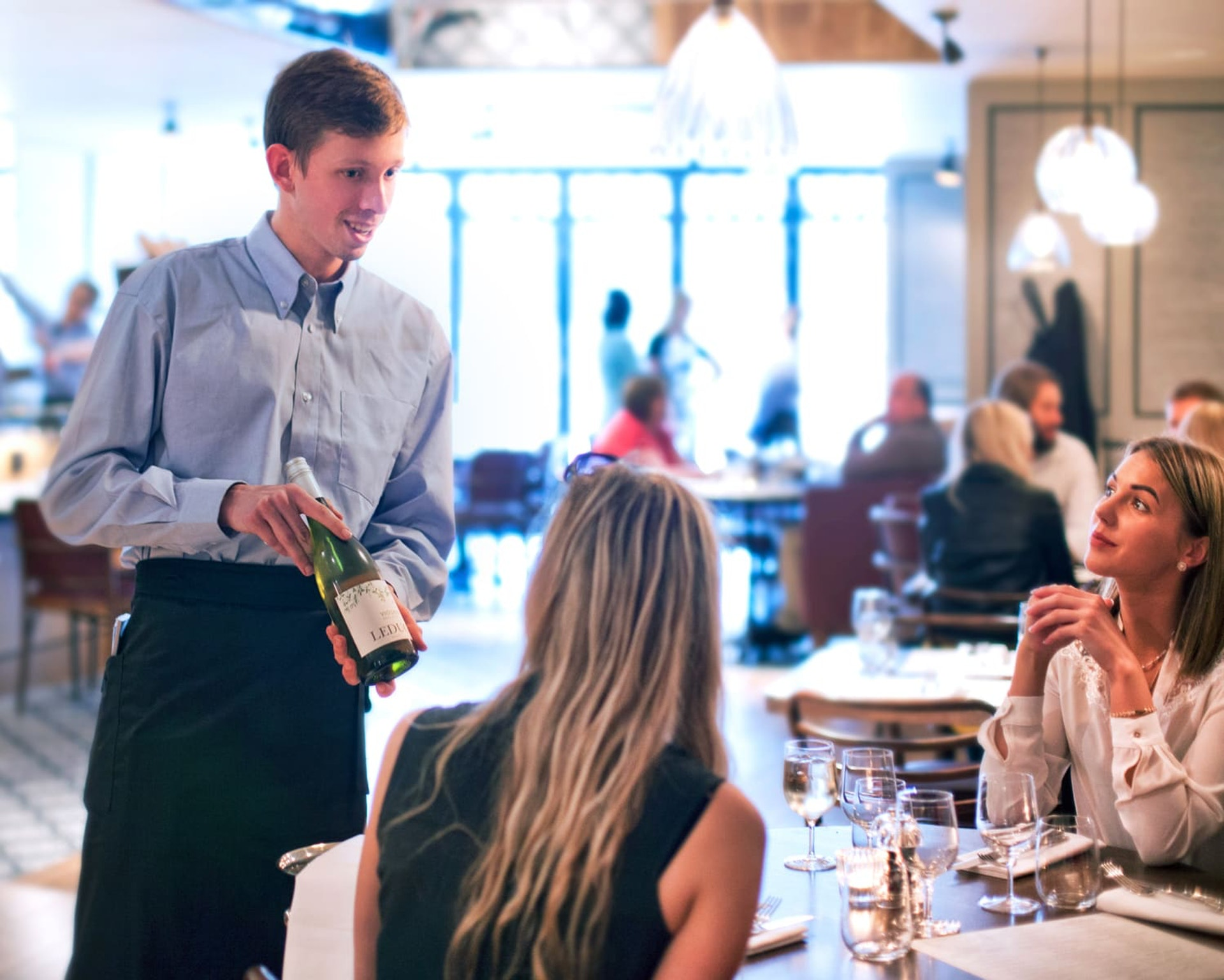 Waiter serving wine in Cote Brasserie restaurant, London