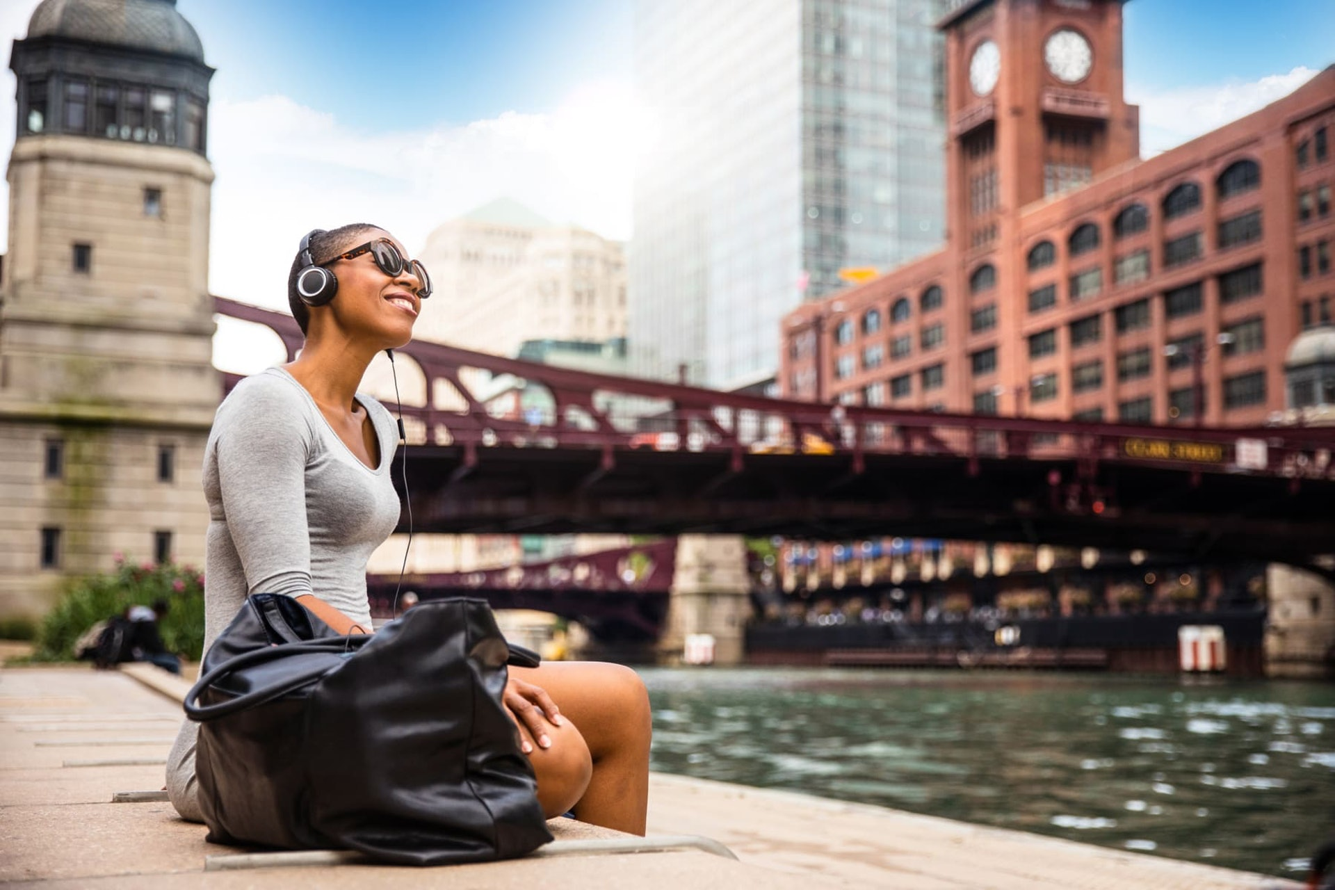 Girl Sitting by River With Headphones in Chicago