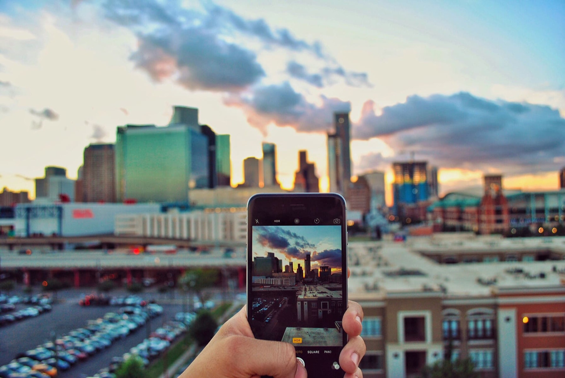 Person taking phone camera photo of skyline in Houston, Texas at sunset