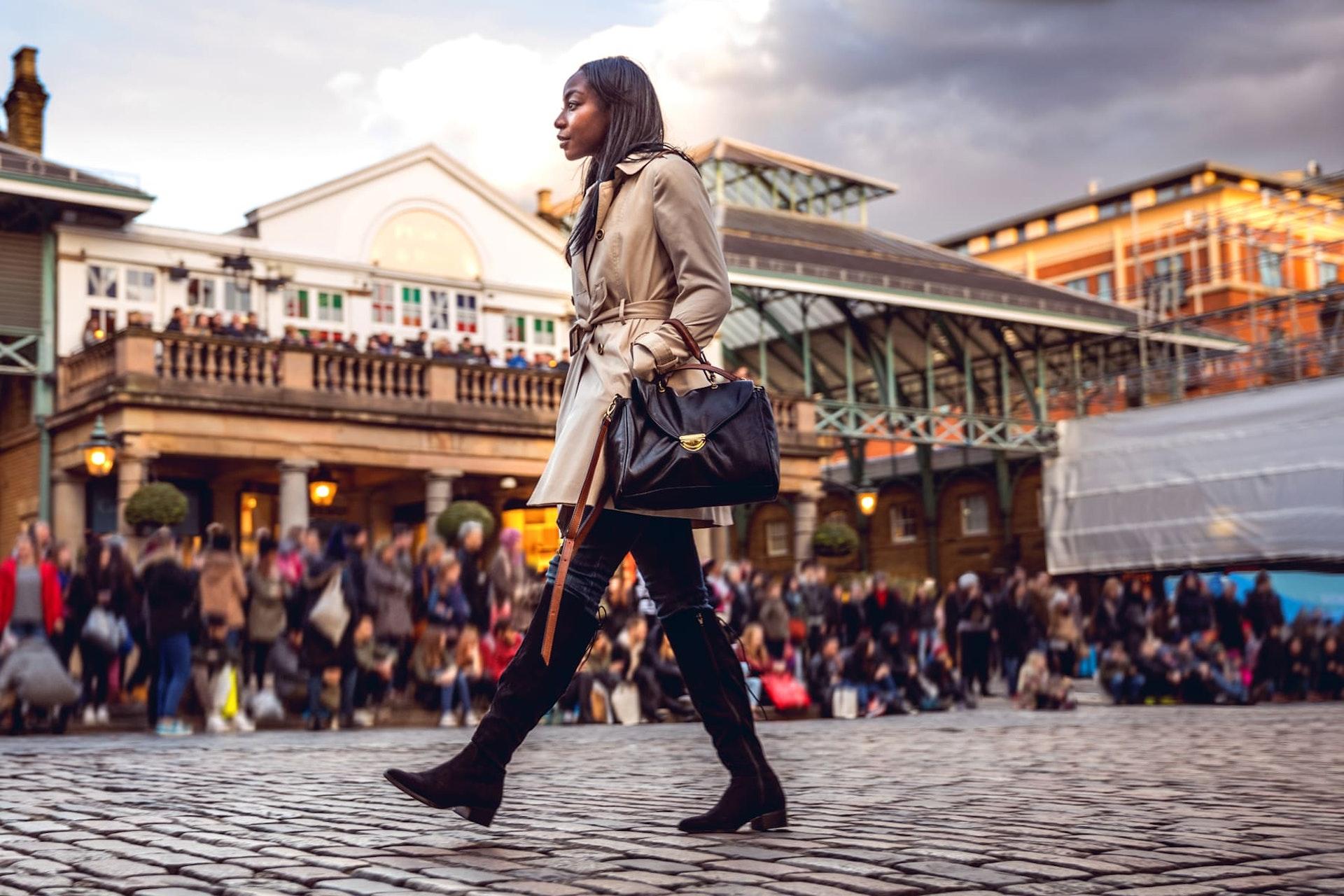 Woman walking past market, London