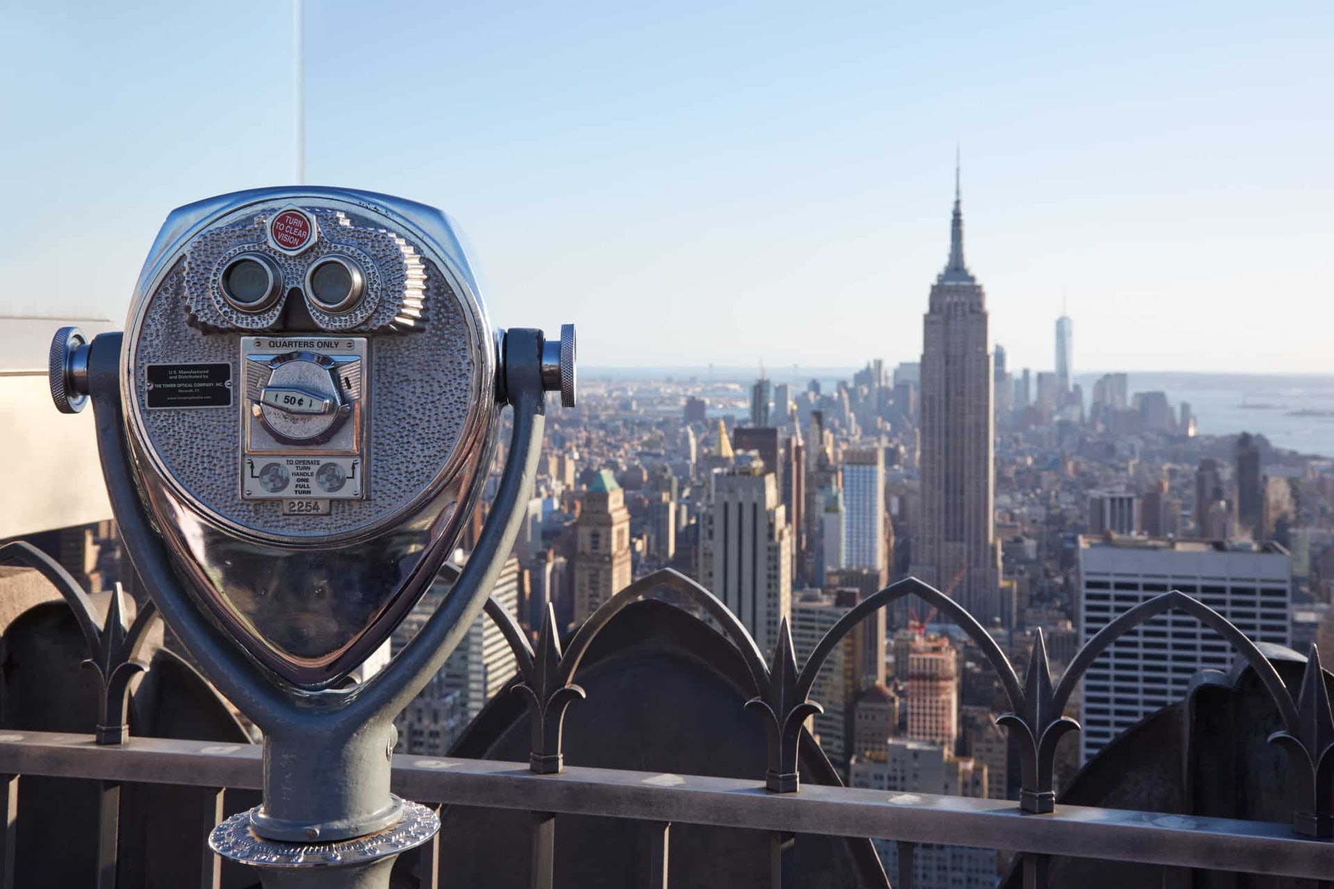 Binoculars on Rockefeller Center with Empire State Building and city view at the end of the day in New York