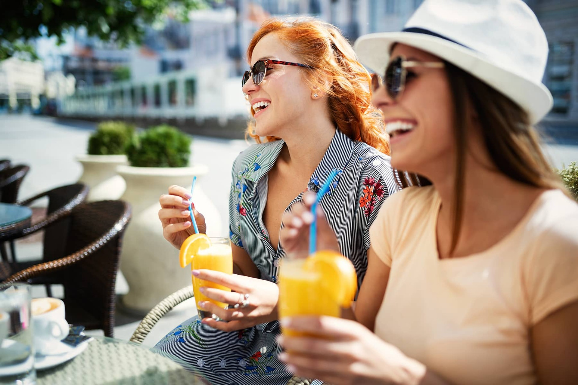 Friends having a great time in cafe. Women smiling and drinking juice and enjoying together